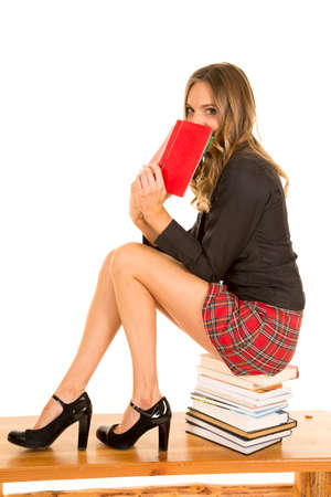 A school girl peeking over a book while she sits on books. Stock Photo