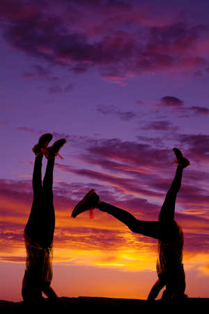 A silhouette of a woman doing a head stand in the outdoors. photo