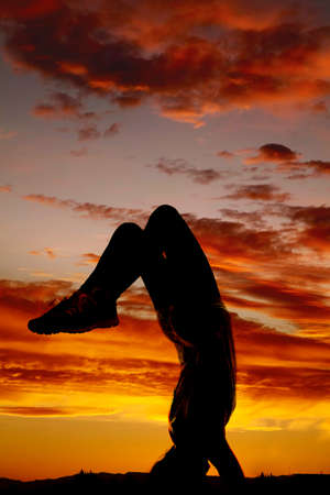 A silhouette of a woman doing a head stand with her legs back. photo