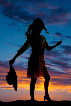 a silhouette of a woman  in her dress holding on to her hat photo