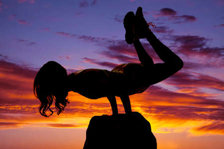 A silouette of  woman doing a yoga strength pose on a rock. photo