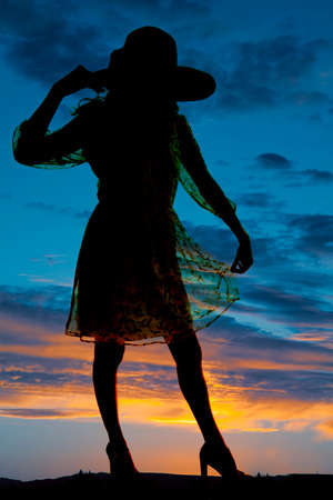 A silhouette of a woman in her sheer dress with a hat on her head. photo