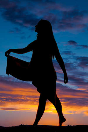 sexual position: A silhouette of a woman holding out her dress walking. Stock Photo