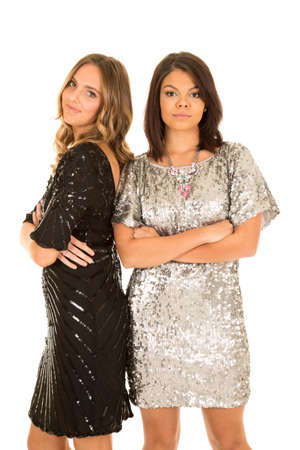 standing together: Two women standing together in their formal shiny dresses, with their arms folded. Stock Photo
