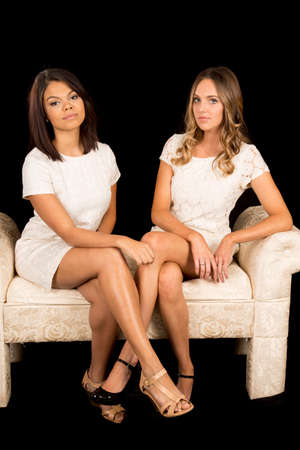 Two women sitting on a bench together with their legs crossed. Stock Photo