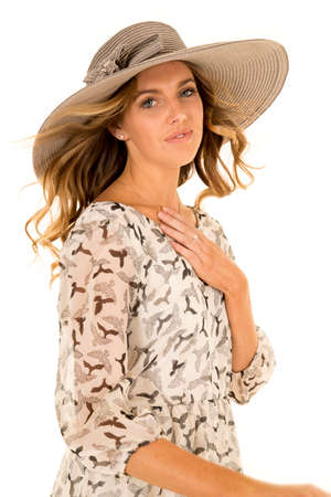 wind blowing: A woman with the wind blowing her hair while wearing a hat. Stock Photo