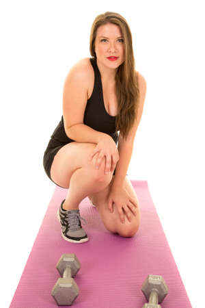 woman kneeling: a woman kneeling down on her fitness mat with weights by her feet. Stock Photo
