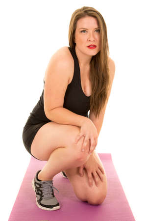a woman kneeling on her fitness mat with a sensual expression. Stock Photo