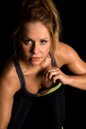 leaning forward: A woman leaning forward in her fitness clothing looking with an intense expression.
