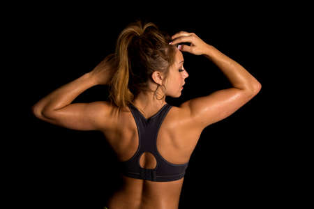 flexing: A womans back flexing in her sports bra close up.