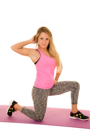 woman kneeling: a woman kneeling and stretching out in her fitness clothes.