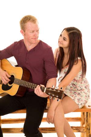 彼の女性の彼のギターを弾く男。自分の顔に笑顔があります。
