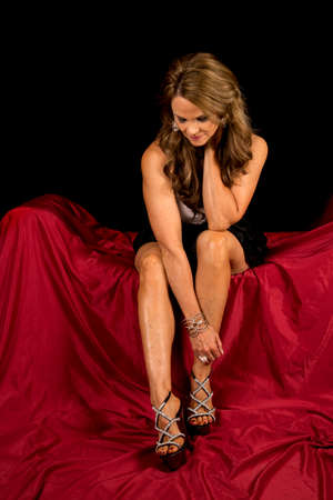 formal dress: A mature woman sitting on a red covered couch in her formal dress, with a black background.