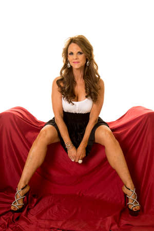 legs apart: A mature woman sitting on her couch with her legs apart in her formal dress.