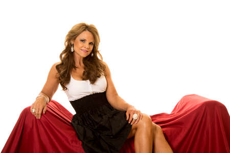 laying on back: A mature woman in her formal dress laying back on her red couch. Stock Photo