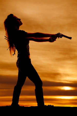 head back: a silhouette of a woman pointing her pistol leaning her head back.