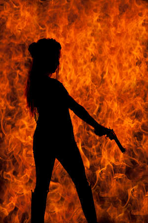 a silhouette of a woman with a fire back ground pointing her gun to the ground. photo