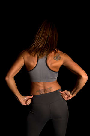 womans clothing: A womans back in her fitness clothing with tattoos on her back and shoulder.