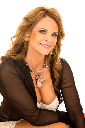 a woman sitting in her sheer top and lace bra with a smile.