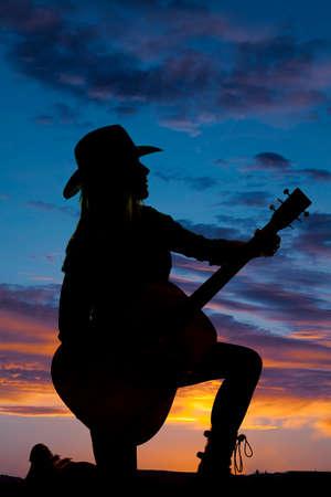 mujer arrodillada: Una silueta de una mujer arrodillada en el suelo, en el aire libre que sostiene a su guitarra. Foto de archivo