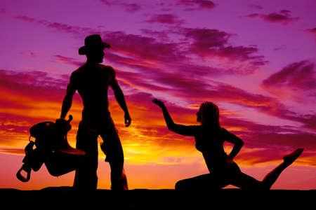 mujer arrodillada: Una silueta de una mujer arrodillada llegar hasta su vaquero que se aferra a la silla de montar.