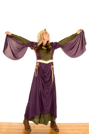 arms out: a woman in her Renaissance dress standing with her arms out and looking up.