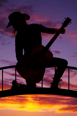 kneeling woman: a silhouette of a woman kneeling on a bridge holding on to her guitar.