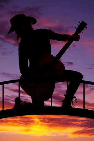 mujer arrodillada: una silueta de una mujer arrodillada sobre un puente que sostiene a su guitarra. Foto de archivo