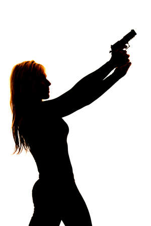 A silhouette of a woman pointing her gun into the sky. photo