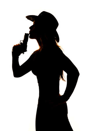 A silhouette of a woman in her western hat blowing on her pistol.