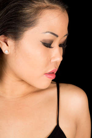 somber: an Asian woman looking down at her shoulder with a somber expression.