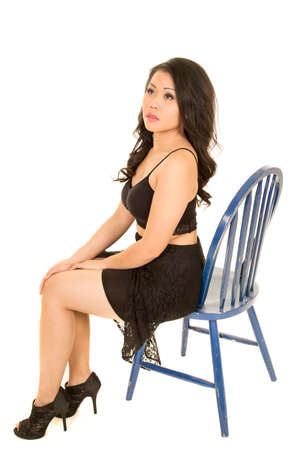 far away look: An Asian woman in her lace dress sittting on a chair with a far away look.