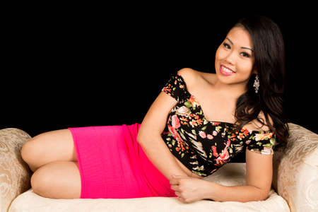 An Asian woman laying on a couch with a smile on her face.