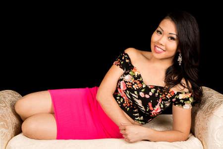 jeune fille: Une femme asiatique portant sur un canap� avec un sourire sur son visage. Banque d'images