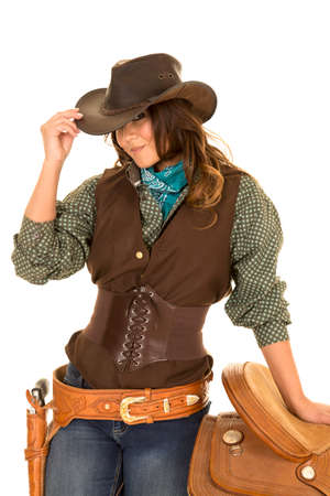 a cowgirl with her hand on the saddle and her other hand touching her hat.