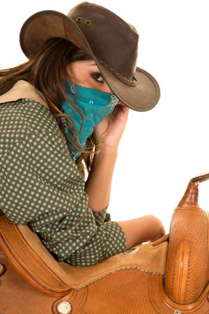 bandana western: a cowgirl leaning on her saddle with a bandana on her face.
