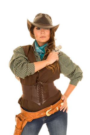 a cowgirl with a serious expression on her face, holding on to her pistol on her shoulder.