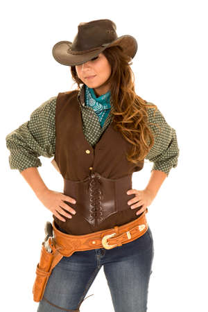 a cowgirl with her hands on her hips looking down.