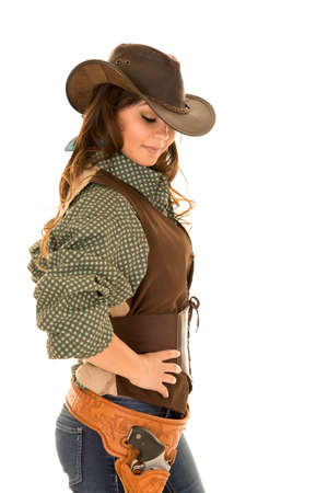 A cowgirl with her hands on her hip, with  a pistol in her holster.