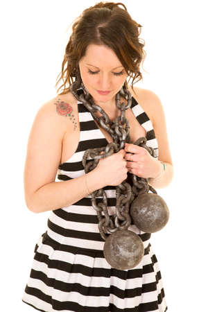 prison ball: A woman with a ball and chain wrapped around her neck, in her prison clothes looking down.