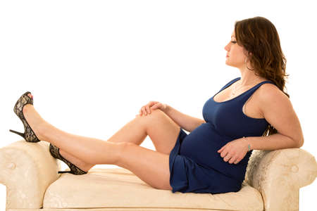 a pregnant woman in her short blue dress sitting on a bench.