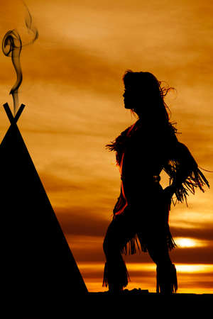 a silhouette of a Indian woman by her teepee, with the wind blowing.