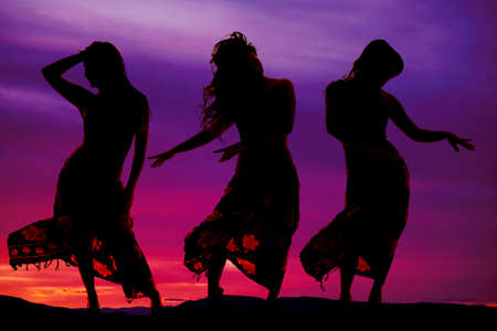 Three women in their sarongs dancing in the outdoors photo