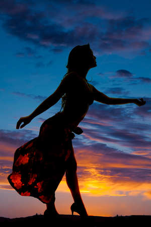 A silhouette of a woman in her sarong reaching out and dancing. photo
