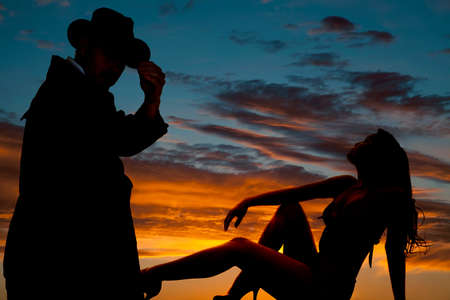 A silhouette of a woman laying back, with a cowboy looking. photo