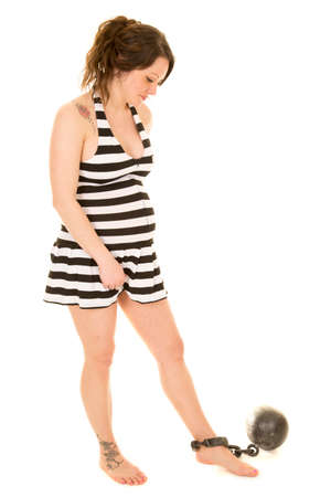 woman prison: A pregnant woman in her prison outfit with a ball and chain around her ankle.  With her tattoos showing.