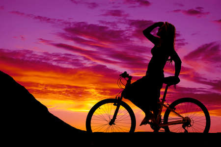cycler: a silhouette of a woman on her bike, resting before heading up a hill.