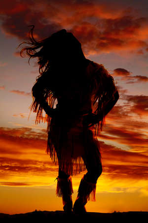wind blowing: a silhouette of a woman in her Indian clothing with the wind blowing her hair. Stock Photo