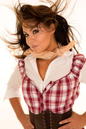 bandana western: A woman in her red plaid top with the wind blowing her hair, with her belt on.