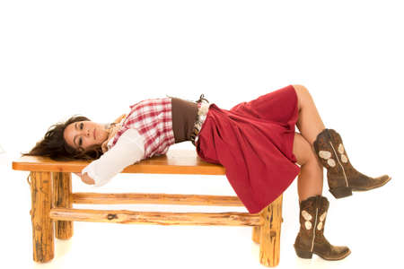 laying on back: A woman laying back on a wooden bench looking. Stock Photo